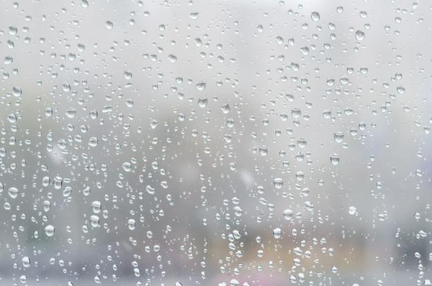 Regendalingen en bevroren water op de achtergrond van het vensterglas