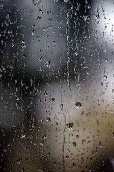 Regendalingen op de oppervlakte van vensterglazen met bokehachtergrond.