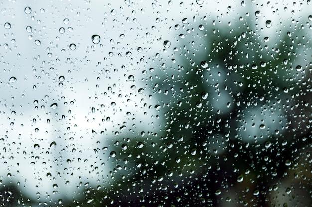 Regendalingen op venster, regenachtige dag. dalingen op de straatregen van de glasvenstertextuur.