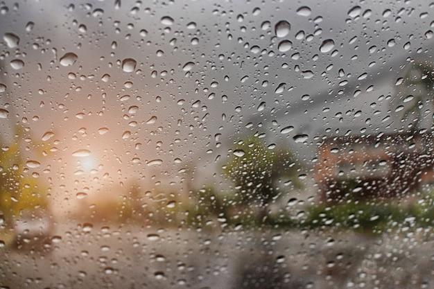 Regendruppel buiten de auto in regenende dag bij straat met zonlicht. goed zicht tijdens reizen.