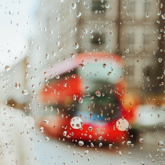 Regendruppel op glas en rode londense bus