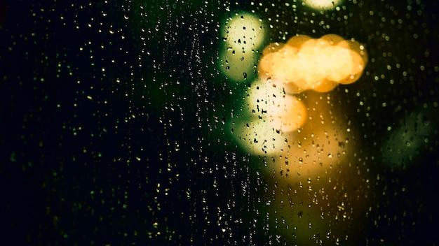 Regendruppel op raam 's nachts. condominium of appartement woonkamer raam op regenseizoen nacht in bangkok thailand. buitenraam is wazig bokeh van regenend stadslicht en natuurlijke boom en lucht.