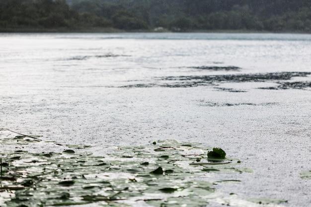Regendruppeleffect op golvend wateroppervlak