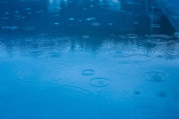 Regendruppels die op een pool of een blauw meer vallen