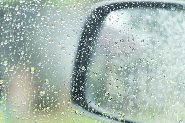 Regendruppels op autoraam en autospiegel op een regenachtige dag