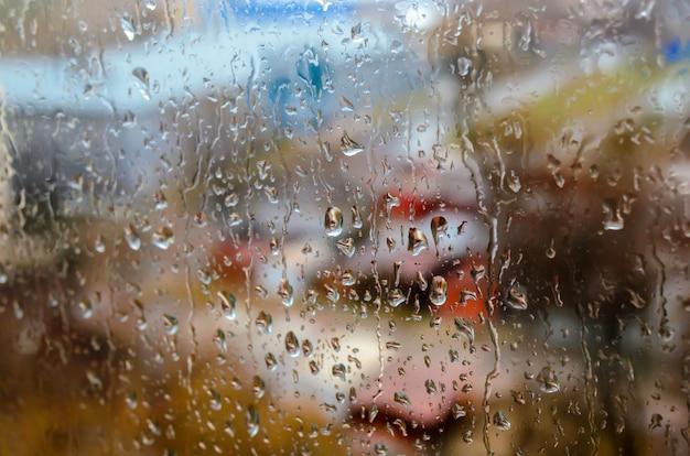 Regendruppels op de achtergrond van het straatvenster