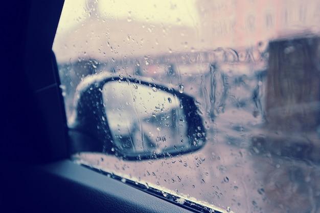 Regendruppels op de autoachteruitkijkspiegel