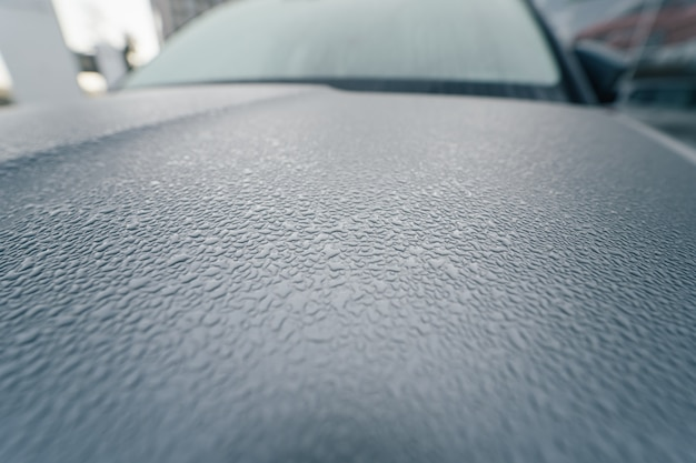 Regendruppels op de motorkap van de auto. detailopname.