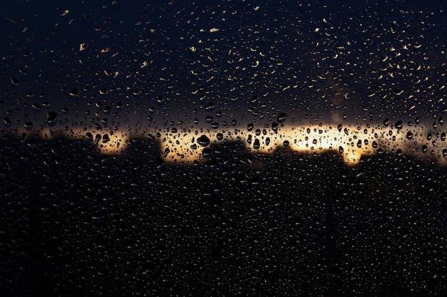 Regendruppels op de ruit. de achtergrond van een nat raam bij zonsondergang. zonsondergang na regen