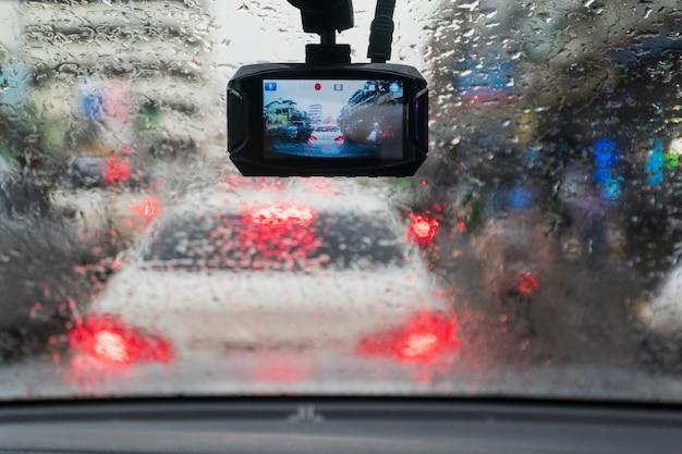 Regendruppels op de voorruit van binnenuit de auto in de file
