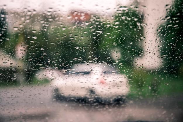 Regendruppels op een autoglas tegen een onscherpe achtergrond met uitzicht op de stad en de lichten van auto's.