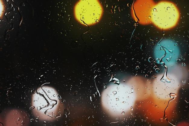 Regendruppels op een autoraam met prachtig onscherpe achtergrond van straat verkeerslichten