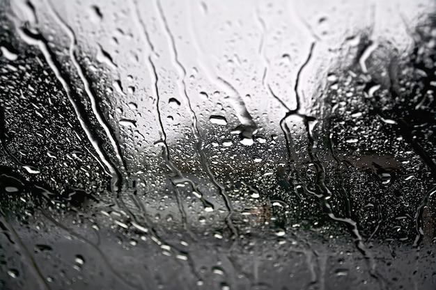Regendruppels op een glazen raam met wazige bomen, weg en grijze auto