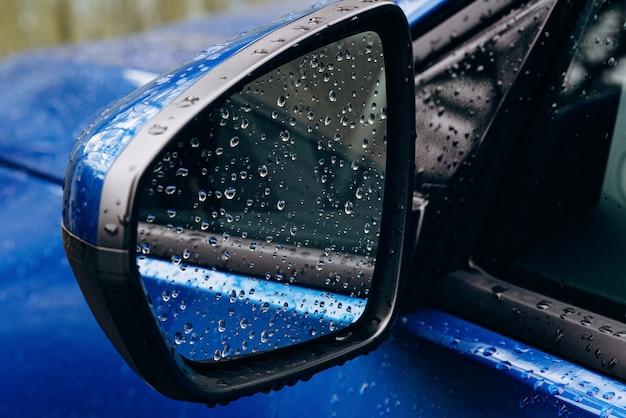 Regendruppels op een spiegel van een blauwe auto. herfst. zachte selectieve focus.