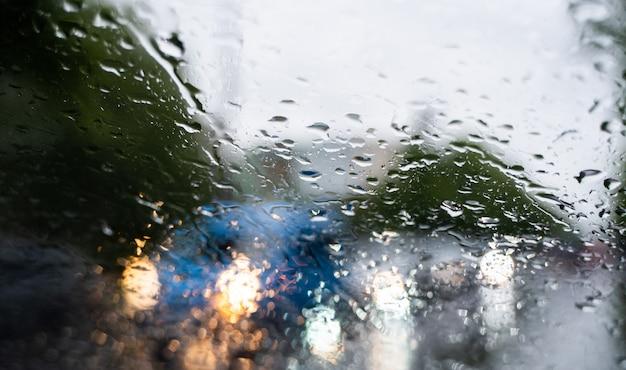 Regendruppels op een voorruitglas met een vage nacht stadslichten op de achtergrond.
