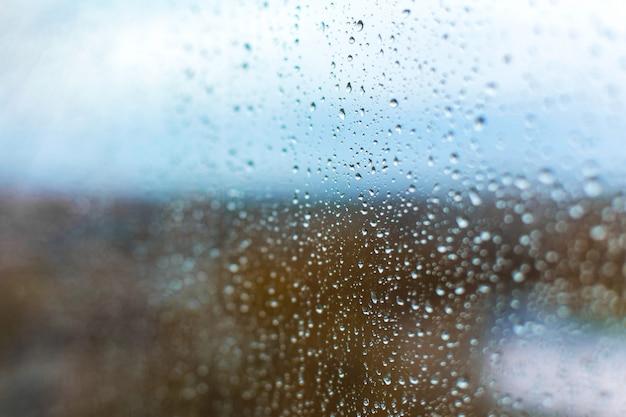 Regendruppels op het glas tegen de achtergrond van de herfststad
