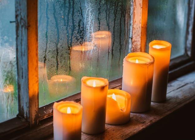 Regendruppels op het raam en brandende kaarsen