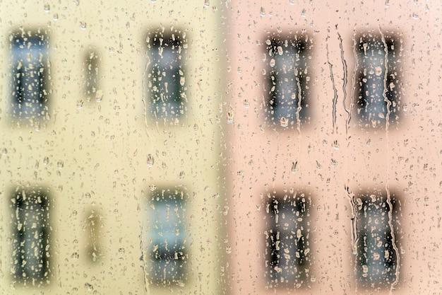 Regendruppels op het raam met uitzicht op de ramen van de woningbouw achtergrond