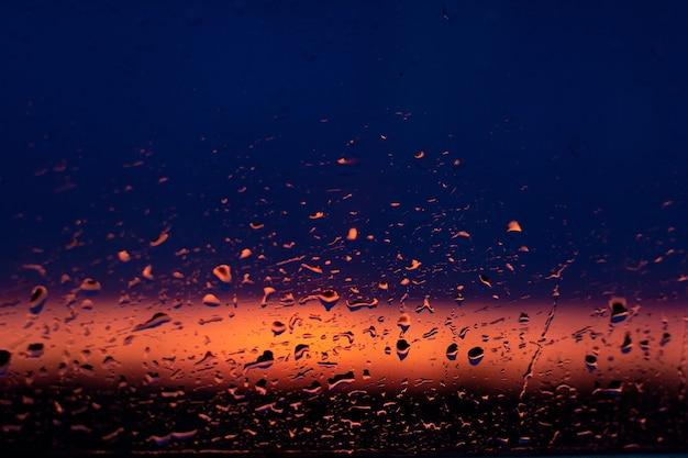 Regendruppels op het raam op de sunsret (donkerblauwe roze achtergrond)