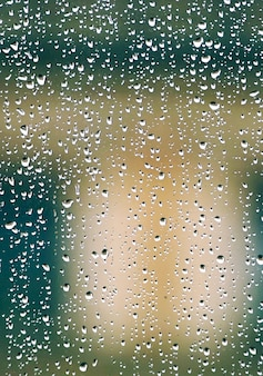 Regendruppels op het raam op regenachtige dagen in het winterseizoen