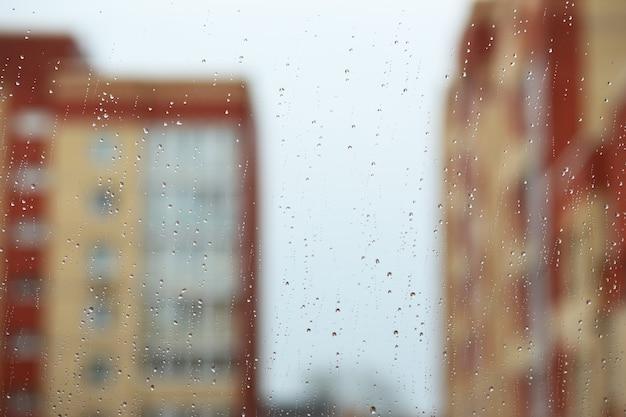 Regendruppels op het raam tegen de stad