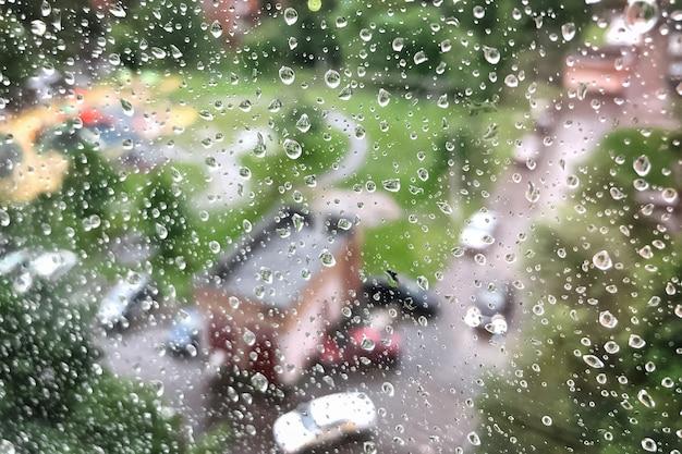 Regendruppels op het vensterglas in regenachtige dag in de zomer