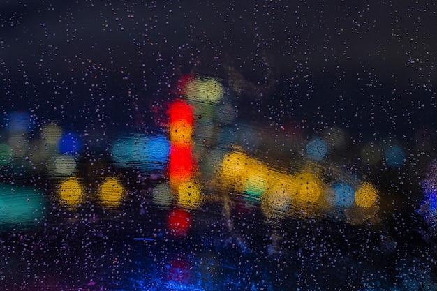 Regendruppels op venster bij nacht met bokehlichten. abstracte achtergrond, waterdaling op het glas, stadslichten bij nacht.