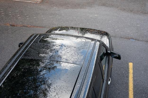 Regendruppels vallen op het dak van zwarte suv-auto op parkeerplaats