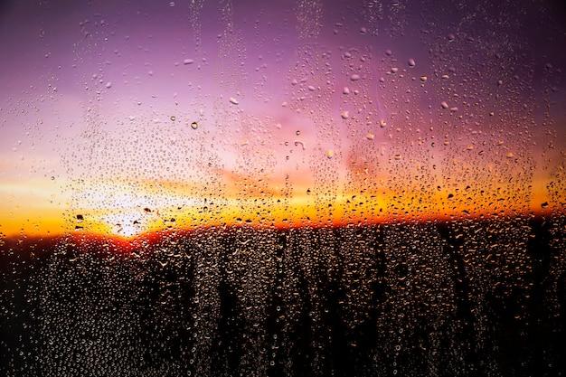 Regeneffect op zonsondergangachtergrond