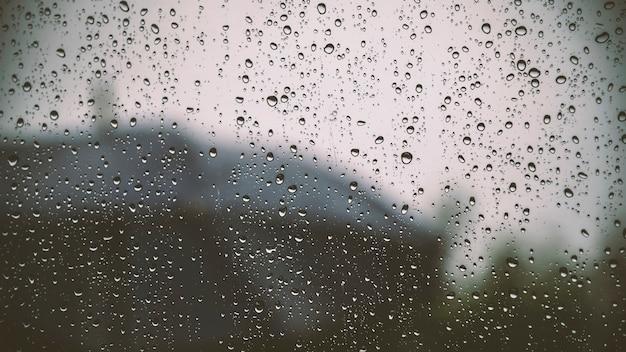 Regent druppels op helder raam in stad buiten