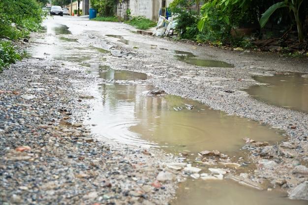 Regenwater opgesloten in een hobbelige weg