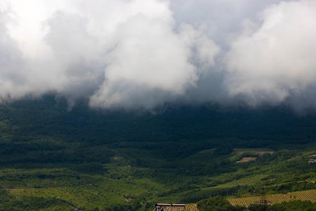 Regenwolken over bergen en een vallei met een groene wijngaard.