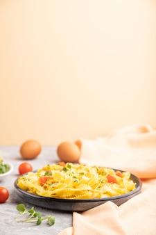 Reginelle griesmeel pasta met tomaat, eieren en microgroene spruiten op een grijze en oranje achtergrond. zijaanzicht, selectieve aandacht.