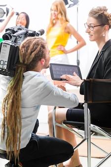 Regisseur die cameraman shoot of scene regie geeft op de set van een videoproductie voor tv, televisie of nieuws