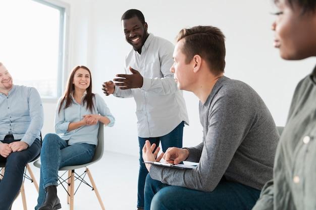 Rehab-patiënten die naar de glimlachende mens luisteren