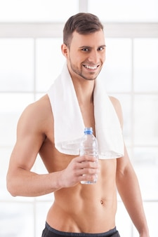 Rehydrateren na de training. knappe jonge gespierde man met handdoek op schouders die een fles water vasthoudt en glimlacht