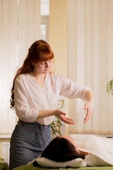 Reiki-genezer reinigt de ether van de patiënt