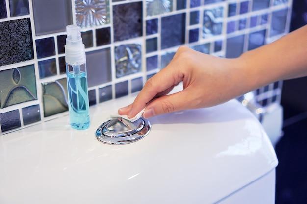 Reinig de toiletspoelknop met de hand door af te vegen met alcoholspray om coronavirus te voorkomen