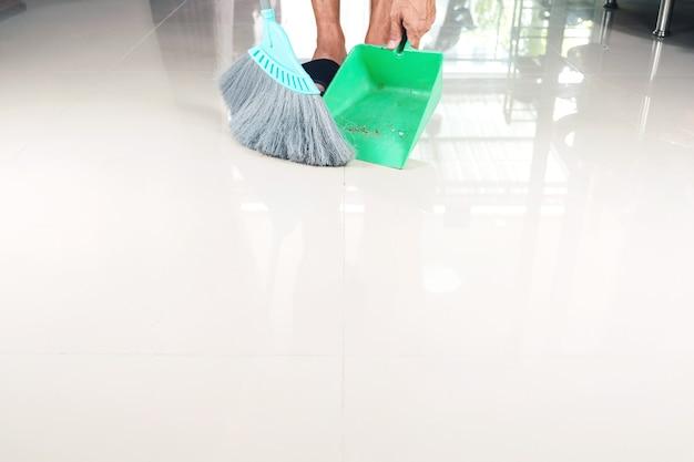 Reinig tegelvloeren met een plastic bezem en stoffer