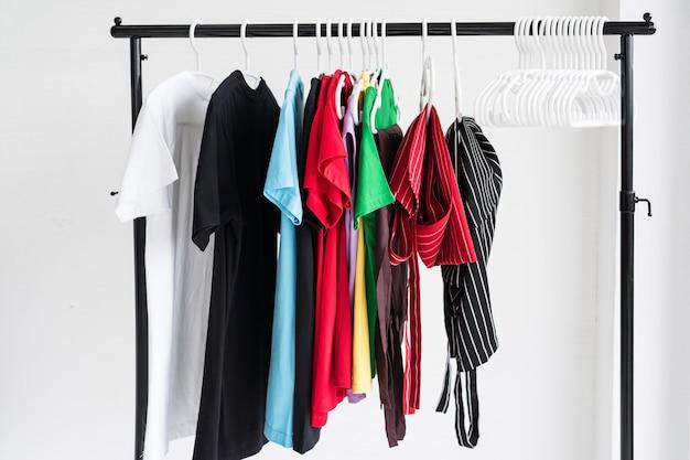 Reinig verschillende t-shirts en schortkleding die na het wassen aan het rek hangt.
