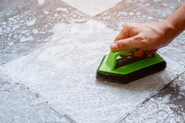 Reinigen van de tegelvloer met een kunststof vloer scrubber.