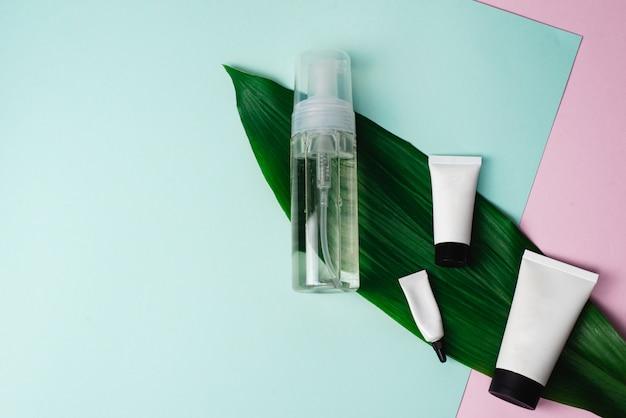 Reinigend schuim of micellair water en verschillende patronen voor crèmes op een palmblad op een pastelroze en blauwe achtergrond. crème voor gezicht, ogen en handen op een moderne achtergrond