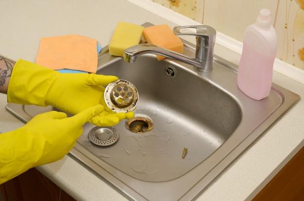 Reiniger in rubberen handschoenen vertoont afval in de plughole-beschermer van een gootsteen