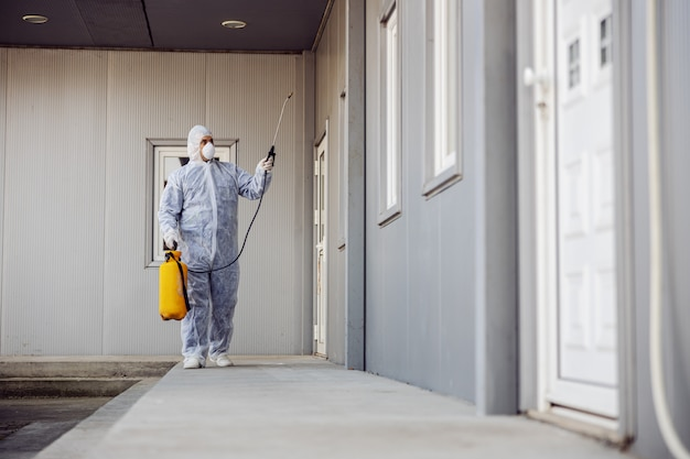 Reiniging en desinfectie buiten rond gebouwen, de coronavirus-epidemie. professionele teams voor desinfectie-inspanningen. infectiepreventie en bestrijding van epidemieën. beschermend pak en masker.