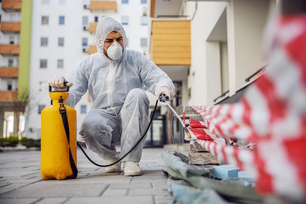 Reiniging en desinfectie buiten rond gebouwen, de covid-19-epidemie. sessieteams voor desinfectie-inspanningen. infectiepreventie en bestrijding van epidemieën. het pak en masker.