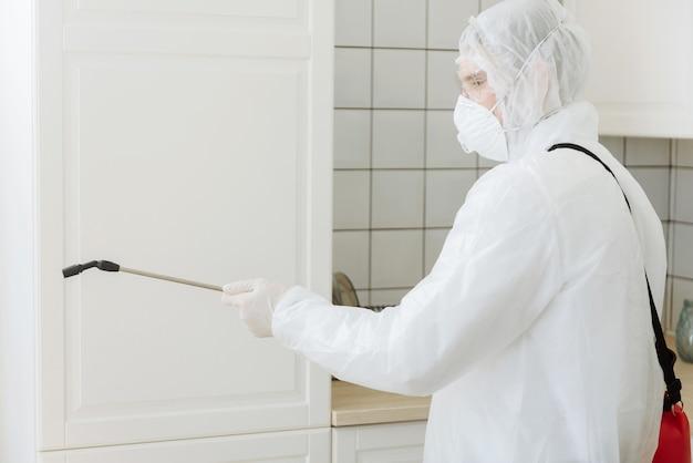 Reiniging en desinfectie in het stadscomplex te midden van de coronavirus-epidemie. professionele teams voor desinfectie-inspanningen. infectiepreventie en bestrijding van epidemieën. beschermend pak en masker