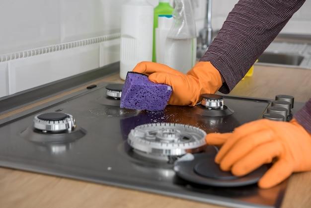 Reiniging in de keuken gassteen met schuim en spons. huishoudelijke apparatuur voor een gezonde levensstijl