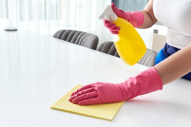 Reiniging van de huistafel het oppervlak van de keukentafel reinigen met een desinfecterende sprayfles en de oppervlakken wassen met een handdoek en handschoenen. covid-19 preventie ontsmetting van binnen.