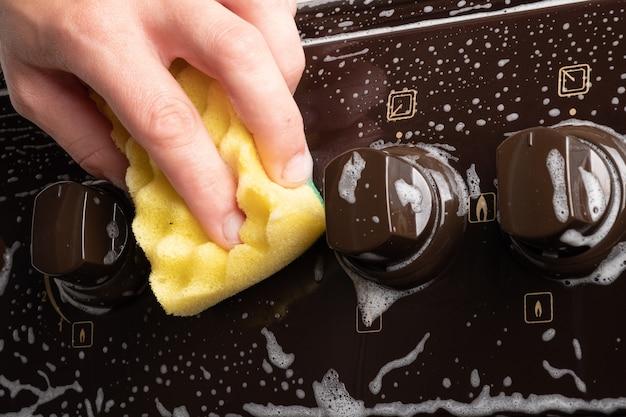 Reiniging van de keuken, oppervlaktereiniging op het gasfornuis, reinigen met schuim en washandje, huishoudelijke keukenapparatuur.