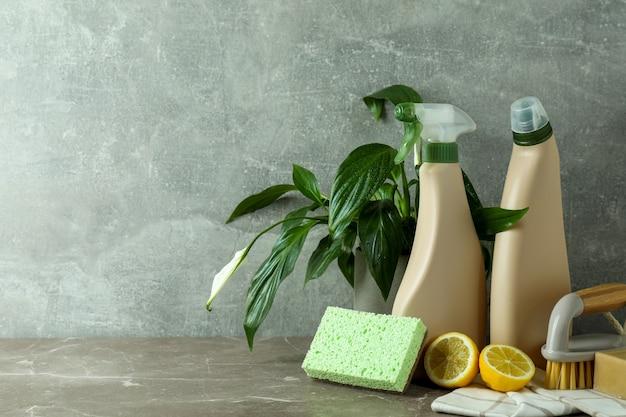 Reinigingsconcept met milieuvriendelijke schoonmaakmiddelen op grijze gestructureerde tafel